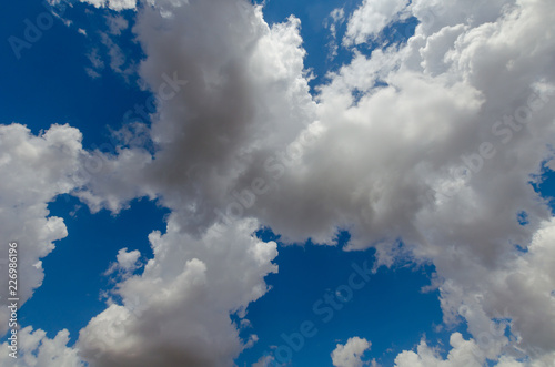 Blue sky, cumulus clouds, sunlight. - 226986196