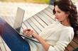 Young woman sitting with a laptop on a park bench. Work outside