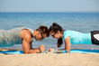 fitness, sport and lifestyle concept - couple doing plank exercise on summer beach