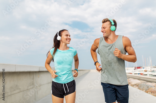 sport, people and technology concept - happy couple with headphones and fitness trackers running outdoors - 226991761