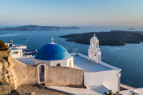 Iconic church with blue dome in Oia, Santorini island, Greece.