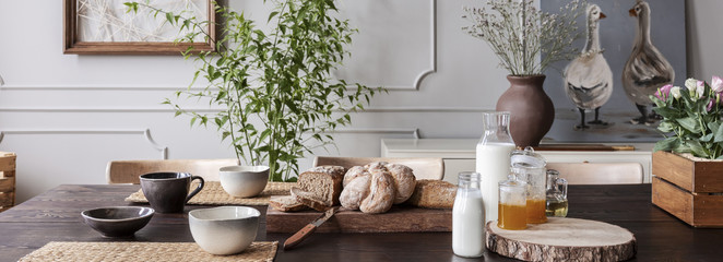 Panorama of wooden table with bowls, bread, milk and honey in grey dining room interior. Real photo