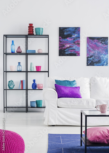 Pillows on white sofa in simple living room interior with posters of cosmos and glass table. Real photo - 226994126