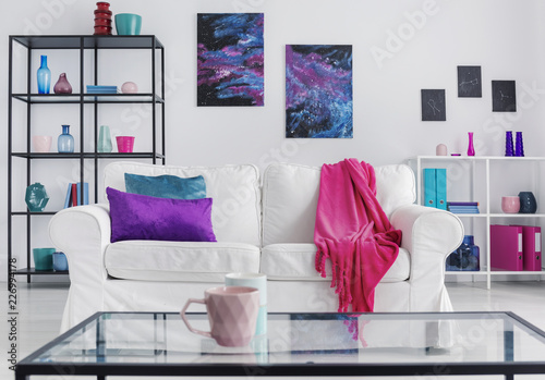 Leinwanddruck Bild Pink mug on table in front of white settee with blanket in apartment interior with posters. Real photo
