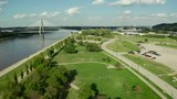A hyperlapse of a fly over a full fly over a river front park with green grass, trees, walkways, town style lamps, and a backgdrop of a busy city bridge & industrial silos & towers. - 227006508