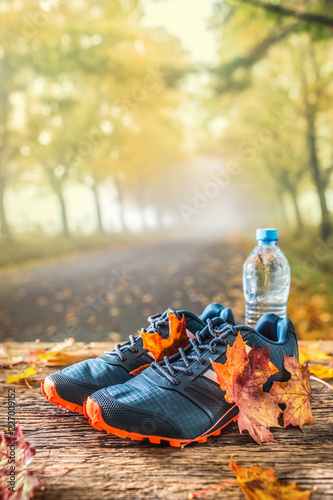 Foto Murales Blue sport shoes and water laid on a wooden board.