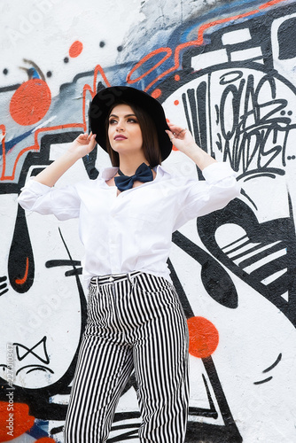 Beautiful female model wearing striped pants, a white shirt and black bow and hat looking up near a graffiti wall