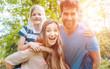 Leinwanddruck Bild - Familie hat Spaß zu viert, der Vater trägt die Töchter huckepack