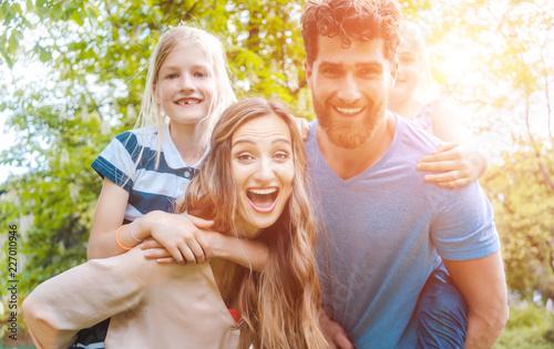 Leinwandbild Motiv Familie hat Spaß zu viert, der Vater trägt die Töchter huckepack