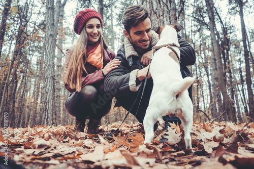 Couple of woman and man playing with their dog in fall