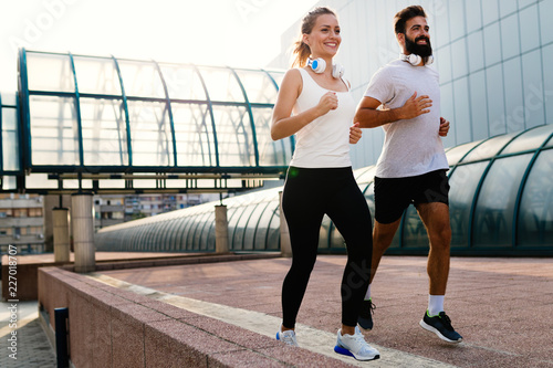 Foto Murales Young fitness couple running in urban area