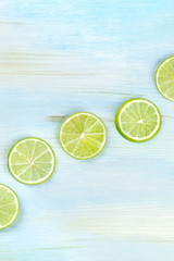 An overhead photo of many vibrant lime slices on a teal blue background with a place for text