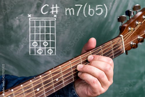 Man in a blue denim shirt playing guitar chords displayed on a blackboard, Chord C sharp minor 7(b5) - 227025322