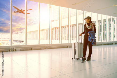 Leinwanddruck Bild single woman and traveling luggage standing in airport terminal building