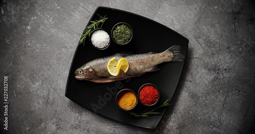 Leinwandbild Motiv From above shot of ceramic plate with assorted aromatic spices and fresh uncooked trout standing on surface of stone tabletop