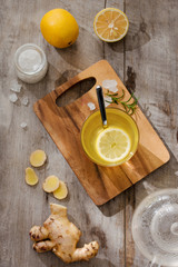 Cup of Ginger tea with lemon. Cup of Ginger tea with lemon. Glass mug of green hot tea on wooden table. Sliced lemons on a chopping board