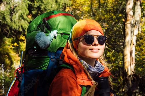 Female tourist hiking in autumn fantastic forest landscape