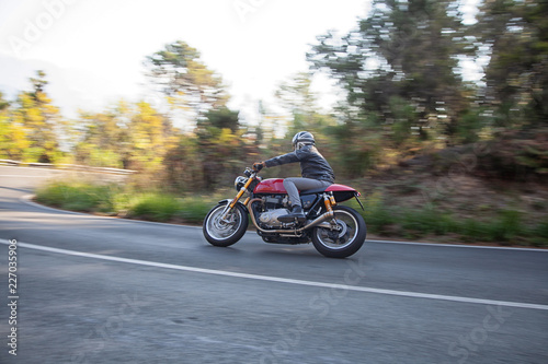 motociclista in piega su strada tortuosa