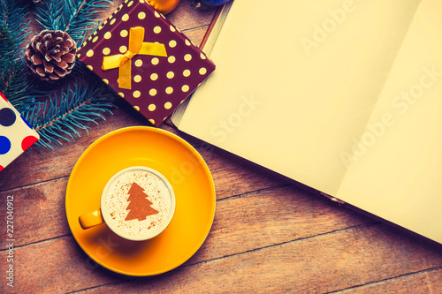 Leinwandbild Motiv yellow cup of Cappuccino with cream Christmas tree and open book on wooden table near toys.