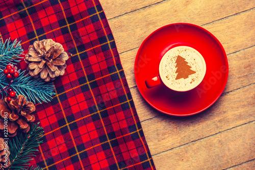 czerwona filiżanka cappuccino z kremową choinką na drewnianym stole.