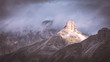 Quadro lit mountain top in between clouds