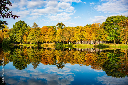 Leinwandbild Motiv Blue sky in the mirror on an autumn lake