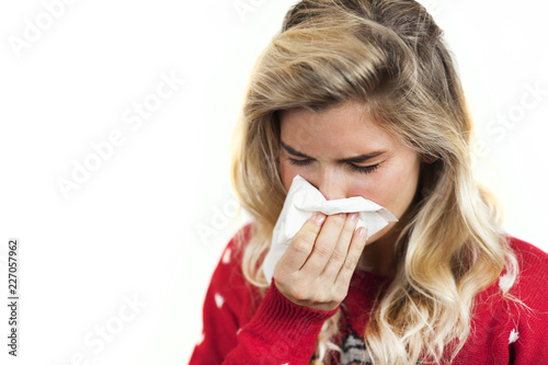Foto Murales Symptoms of flu or allergies. Strong young European woman with fever, sneezing in a tissue, allergy, cold, with copy space, young girl, portrait of a sick woman, isolated on a white background.