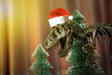 Dinosaur fossil skeleton Tyrannosaurus Rex ( t-rex ) wearing a Santa Claus hat and decorated with pine trees Christmas in the bedroom with background pink curtains.