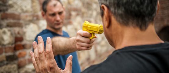 Robber with a gun attacks the victim. Gun point