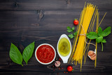 The thin spaghetti on black wooden background. Yellow italian pasta with ingredients. Italian food and menu concept. - 227066187