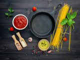 The thin spaghetti on black wooden background. Yellow italian pasta with ingredients. Italian food and menu concept. - 227066307