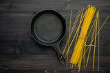The thin spaghetti on black wooden background. Yellow italian pasta with copy space . Italian food and menu concept. - 227066381
