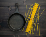 The thin spaghetti on black wooden background. Yellow italian pasta with copy space . Italian food and menu concept. - 227066397