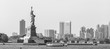 Statue of Liberty with Liberty State Park and Jersey City skyscrapers in background, USA. Black and white image.