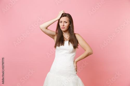 Portret zaniepokojona zaintrygowana panny młodej kobieta w białym ślubnej sukni stojaku problem utrzymuje rękę na głowie odizolowywającej na różowym pastelowym tle. Koncepcja uroczystości weselne. Skopiuj miejsce na reklamę.