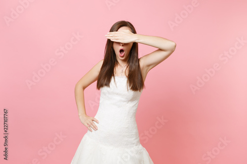 Portret szokująca panny młodej kobieta z rozpieczętowanym usta w koronkowej białej ślubnej sukni nakrycia oczach z palmą odizolowywającą na pastel menchii tle. Koncepcja uroczystości weselne. Skopiuj miejsce na reklamę.