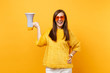 Portrait of cheerful attractive young woman in fur sweater orange heart eyeglasses holding megaphone isolated on bright yellow background. People sincere emotions, lifestyle concept. Advertising area.