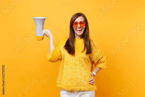 Portrait of cheerful attractive young woman in fur sweater orange heart eyeglasses holding megaphone isolated on bright yellow background. People sincere emotions, lifestyle concept. Advertising area. © ViDi Studio