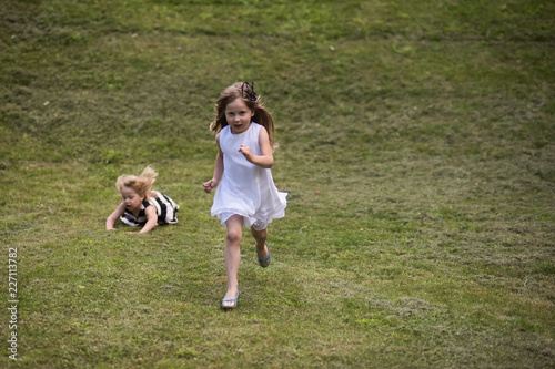 Foto Murales Kids run and fall on green grass on summer day