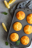 Homemade lemon muffins in black teflon baking dish over grey concrete background. Copy space.