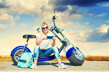 Girl biker sits on a motorcycle. Relax after the trip.