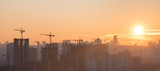 Panorama of sunset in the city with silhouette of buildings and industrial cranes