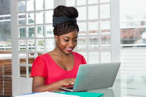 Fototapeta Afrikanische Frau arbeitet am Laptop