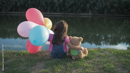 Loneliness. A child with a toy and balloons looks at the river. Back view.