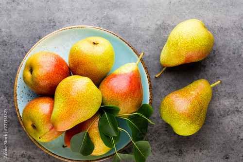 Foto Murales Fresh bio pear with leaves on the plate. Gray stone table.
