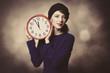 Portrait of beautiful women in blue dress with huge clock on grey background.