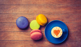 Cup of Cappuccino with heart shape symbol and macarons on wooden background