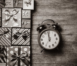 Different color gift boxes and alarm clock on wooden background. Image in black and white color style - 227154395
