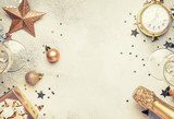 Christmas or New Year composition, frame, pink background with gold Christmas decorations, stars, snowflakes, balls, alarm clock, gift box and bottle of champagne, top view - 227163553