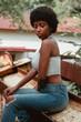 mujer negra afro descendiente sentada sobre metales oxidados